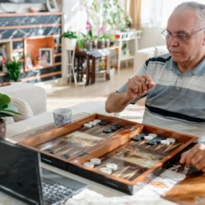 Senior citizen plays backgammon against someone on computer on Zoom call